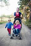 Mother with two children pushing baby carriage on country road Stock Photo - Premium Royalty-Free, Artist: Blend Images, Code: 698-06117039