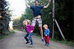 Excited father with two children jumping on country road Stock Photo - Premium Royalty-Free, Artist: Cultura RM, Code: 698-06117045