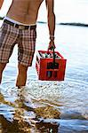 Midsection of a man knee deep in water carrying drinks crate Stock Photo - Premium Royalty-Free, Artist: Photocuisine, Code: 698-06117059