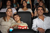 Family enjoying movie in theater, boy resting head on his mother's shoulder Stock Photo - Premium Royalty-Freenull, Code: 632-06118249