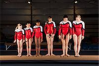 Female gymnasts of various ages standing in a row on balance beam Stock Photo - Premium Royalty-Freenull, Code: 632-06118279
