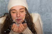 Young woman wearing winter clothing, blowing handful of confetti Stock Photo - Premium Royalty-Freenull, Code: 632-06118488