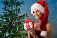 snowflakes  holiday - Woman wearing Santa hat and holding Christmas present, portrait Stock Photo - Premium Royalty-Freenull, Code: 632-06118583