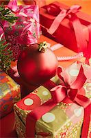 present wrapped close up - Christmas ornament resting on festively wrapped gifts Stock Photo - Premium Royalty-Freenull, Code: 632-06118747