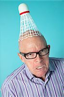 Portrait of angry senior man with shuttlecock on head over colored background Stock Photo - Premium Royalty-Freenull, Code: 693-06120721