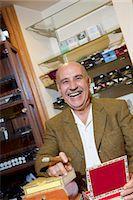 Portrait of cheerful mature man smoking cigar in tobacco store Stock Photo - Premium Royalty-Freenull, Code: 693-06120807