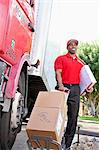 Young African American male standing with packages near delivery truck Stock Photo - Premium Royalty-Free, Artist: Cultura RM, Code: 693-06120823