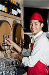 Portrait of a young waiter standing by drinks tap Stock Photo - Premium Royalty-Free, Artist: Blend Images, Code: 693-06120849
