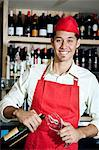 Portrait of a happy young waiter with bottle and glass Stock Photo - Premium Royalty-Free, Artist: Blend Images, Code: 693-06120850
