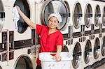 Portrait of a happy young female employee putting clothes in washer Stock Photo - Premium Royalty-Free, Artist: CulturaRM, Code: 693-06120897