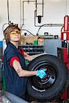 Portrait of a confident young female mechanic carrying tire in vehicle repair shop Stock Photo - Premium Royalty-Free, Artist: Blend Images, Code: 693-06120963