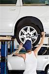 Back view of young female working on car tire in workshop Stock Photo - Premium Royalty-Free, Artist: Cusp and Flirt, Code: 693-06120976