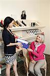 Happy mature customer taking footwear box from mid adult female salesperson in shoe store Stock Photo - Premium Royalty-Free, Artist: Raymond Forbes, Code: 693-06121143