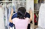 Back view of a mid adult employee putting plastic on dry cleaned clothes Stock Photo - Premium Royalty-Free, Artist: CulturaRM, Code: 693-06121197