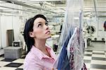 Beautiful woman looking up in laundry Stock Photo - Premium Royalty-Free, Artist: Blend Images, Code: 693-06121200
