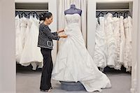 Side view of a mature employee adjusting elegant wedding dress in bridal store Stock Photo - Premium Royalty-Freenull, Code: 693-06121245