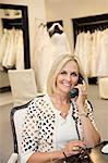 Portrait of a happy woman listening to telephone receiver in bridal store Stock Photo - Premium Royalty-Free, Artist: Photocuisine, Code: 693-06121264