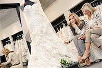 Mother and daughter sitting on sofa while looking at elegant wedding dress in bridal store Stock Photo - Premium Royalty-Freenull, Code: 693-06121272