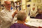 Happy man cutting senior customer's hair with razor Stock Photo - Premium Royalty-Free, Artist: Ikon Images, Code: 693-06121296