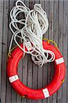 Safe support  circle with rope. Rescue water red life buoy on wooden background of ship or boat. Helpful object.