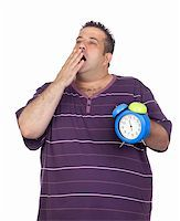 Fat man with a blue alarm yawning clock isolated on white background Stock Photo - Royalty-Freenull, Code: 400-06140395