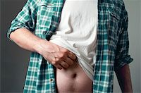 Casually dressed man is scratching his belly Stock Photo - Royalty-Freenull, Code: 400-06141962