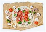 A raw pizza with salami and mushrooms on baking paper Stock Photo - Premium Royalty-Free, Artist: Westend61, Code: 659-06153056