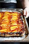 Hands holding a peach tart on a baking tray Stock Photo - Premium Royalty-Free, Artist: Photocuisine, Code: 659-06155038