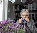 Woman drinking coffee at window Stock Photo - Premium Royalty-Free, Artist: CulturaRM, Code: 649-06164523