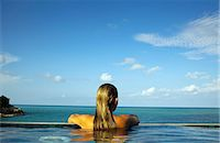 Woman relaxing in infinity pool Stock Photo - Premium Royalty-Freenull, Code: 649-06164845