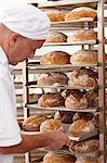 Chef putting tray of bread on rack Stock Photo - Premium Royalty-Free, Artist: Blend Images, Code: 649-06165048