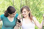 Teenage girls using cell phone on swings