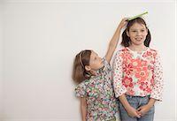 Girl measuring taller sister Stock Photo - Premium Royalty-Freenull, Code: 649-06165192