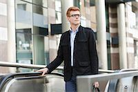 Businessman standing on escalator Stock Photo - Premium Royalty-Freenull, Code: 6108-06166048
