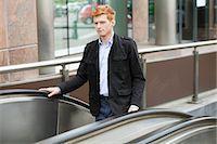 Businessman standing on escalator moving up Stock Photo - Premium Royalty-Freenull, Code: 6108-06166059