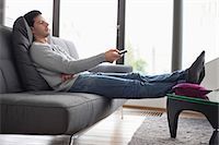 Man reclining on a couch and watching television Stock Photo - Premium Royalty-Freenull, Code: 6108-06166312