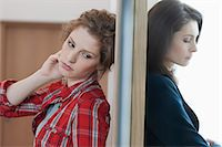 Two female friends standing back to back against a door Stock Photo - Premium Royalty-Freenull, Code: 6108-06166369