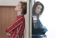 Two female friends standing back to back against a door Stock Photo - Premium Royalty-Freenull, Code: 6108-06166371