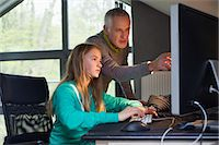 Girl using a computer with her father at home Stock Photo - Premium Royalty-Freenull, Code: 6108-06166610