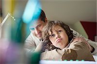 Boy thinking while studying with his father at home Stock Photo - Premium Royalty-Freenull, Code: 6108-06166611