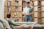 Man talking to his mother reclining on a couch Stock Photo - Premium Royalty-Free, Artist: Westend61, Code: 6108-06166613