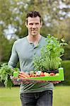 Man holding a tray of raw vegetables Stock Photo - Premium Royalty-Free, Artist: photo division, Code: 6108-06166703