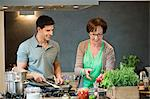 Woman assisting her son to cook food in the kitchen Stock Photo - Premium Royalty-Freenull, Code: 6108-06166715