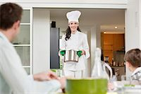 Woman serving food to her family Stock Photo - Premium Royalty-Freenull, Code: 6108-06166739