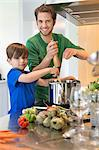 Boy assisting his father in the kitchen Stock Photo - Premium Royalty-Freenull, Code: 6108-06166742