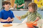 Children cooking in the kitchen with their parents in the background Stock Photo - Premium Royalty-Free, Artist: Cultura RM, Code: 6108-06166767