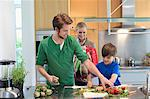 Parents looking at their son cutting vegetables in the kitchen Stock Photo - Premium Royalty-Freenull, Code: 6108-06166784