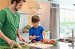 Man looking at his son cutting vegetables in the kitchen Stock Photo - Premium Royalty-Freenull, Code: 6108-06166790