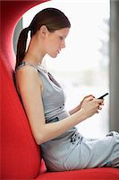 Businesswoman text messaging on a mobile phone in an office Stock Photo - Premium Royalty-Freenull, Code: 6108-06166866