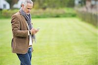 Man text messaging on a mobile phone in a park Stock Photo - Premium Royalty-Freenull, Code: 6108-06166896